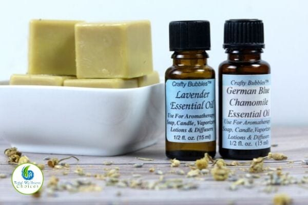 Solid lotion bars in a bowl and essential oil bottles